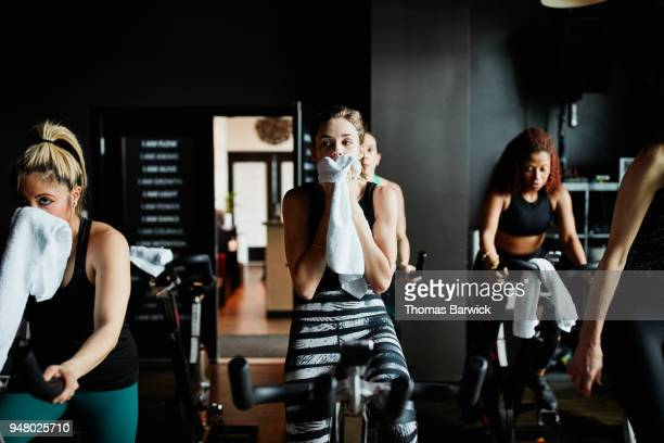 Woman wiping sweat from face with towel during indoor cycling class in fitness studio