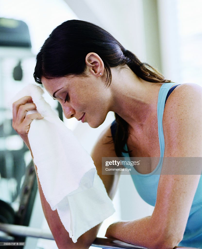 Towel To Wipe Sweat: Woman Wiping Sweat With Towel In Gym Side View Stock Photo