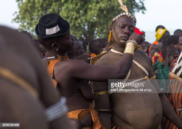 Woman wiping the sweat of a Bodi tribe fat man during Kael ceremony Omo valley Hana Mursi Ethiopia on June 4 2017 in Hana Mursi Ethiopia