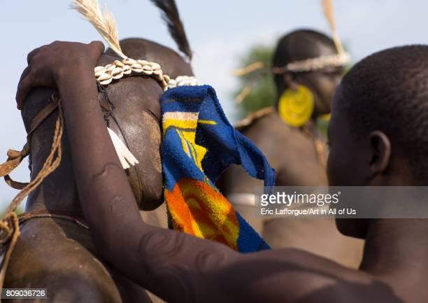 Woman wiping the sweat of a Bodi tribe fat man during Kael ceremony Omo valley Hana Mursi Ethiopia on June 4 2017 in Hana Mursi Ethiopia