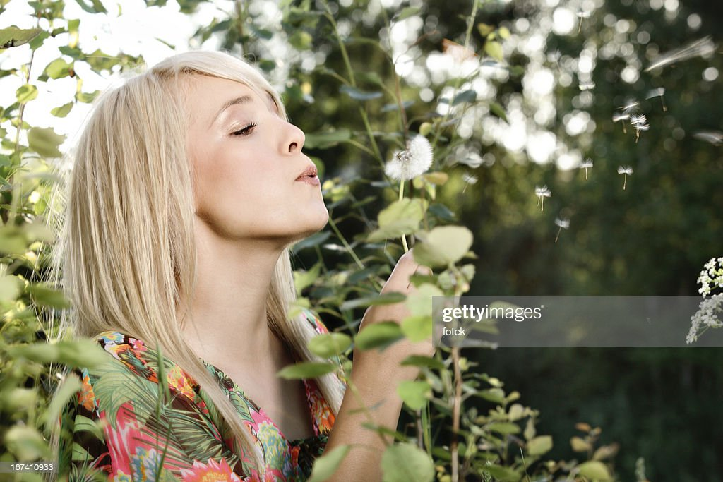 Woman wishing on a dandelion : Stock Photo
