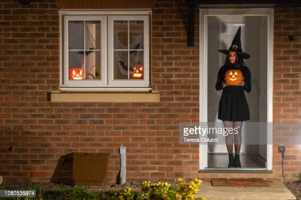 woman witch at the door carrying a pumpkin for halloween night - carving craft product stock pictures, royalty-free photos & images