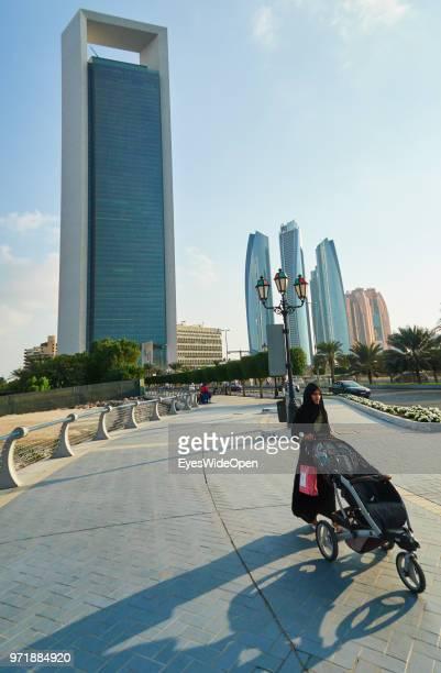 A woman with a baby buggy between skyscrapers at Saadiyat Island on November 27 2015 in Abu Dhabi Emirate Abu Dhabi