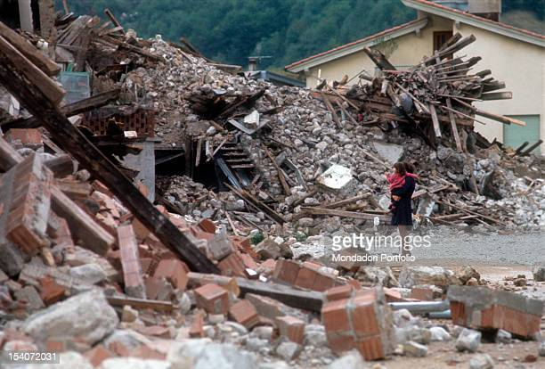 A woman with a baby girl in her arms looks at the ruins of a house destroyed by the earthquake FriuliVenezia Giulia May 1976