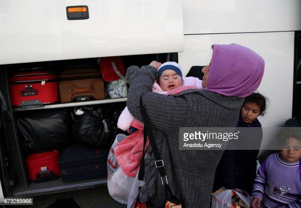 A woman with a baby is seen as 250 Iraqi people who left their homes due to clashes between Iraqi forces and Daesh terrorist organization return...