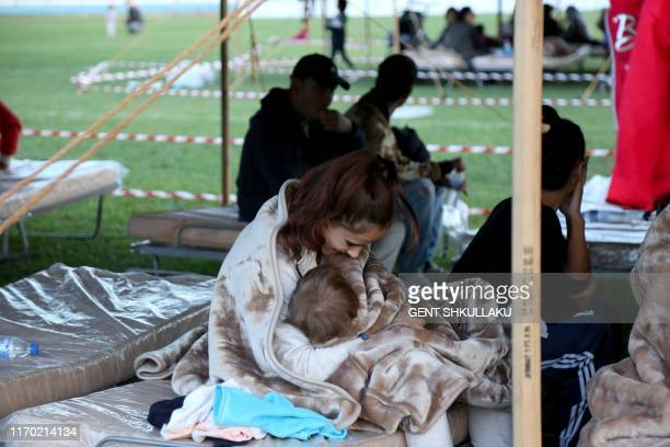 A woman with a baby sits in a makeshift tent at the soccer stadium in Durres on September 22 after two earthquakes over 50 magnitude struck the...