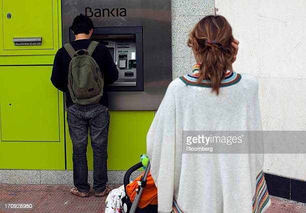 A woman with a baby stroller waits to use an automated teller machine outside a Bankia SA branch in Madrid Spain on Wednesday June 19 2013 Bailing...