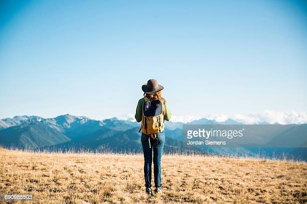 A woman with a backpack overlooking mountains.
