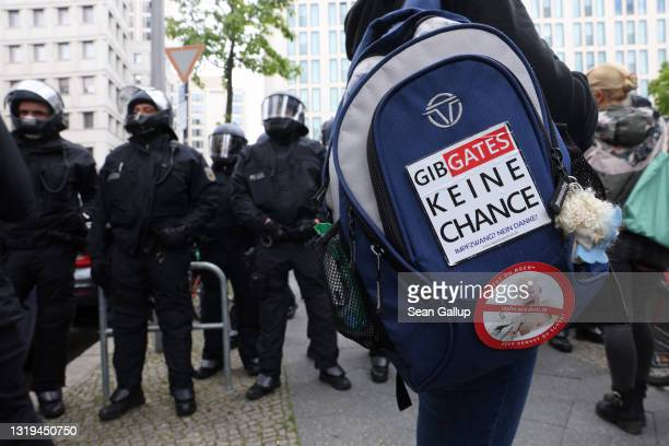 """Woman with a backpack that reads: """"Don't give Gates a chance"""", in reference to Bill Gates, while confronting riot police at a gathering of several..."""