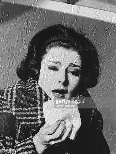 A woman with a bad cold on a rainy day circa 1960