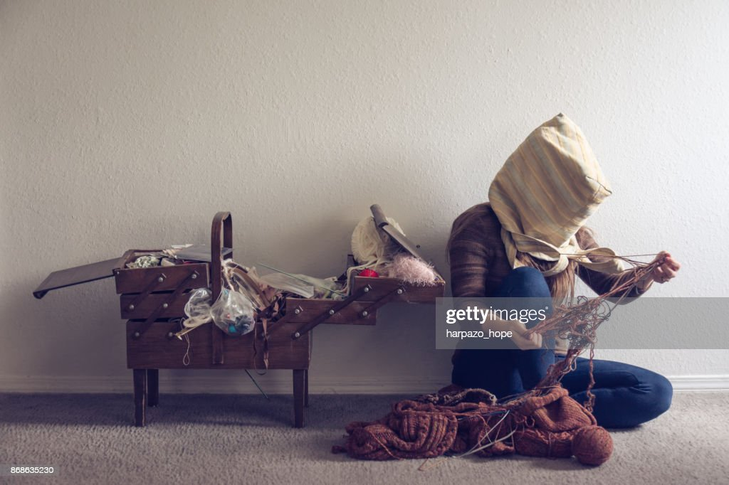 Woman with a bag on her head untangling yarn. : Stock Photo