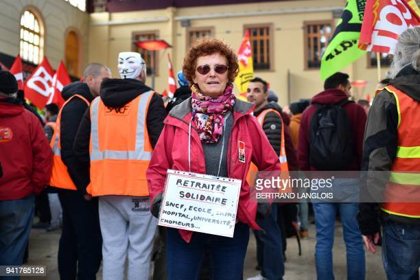 A woman with a banner reading 'solidary pension' attends a rally called by French trade union CGT at SaintCharles train station in Marseille on April...
