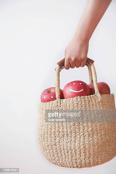 A woman with a basket containing apple
