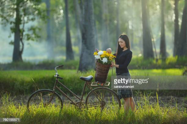 Woman with a basket of flowers on her bicycle, Thailand