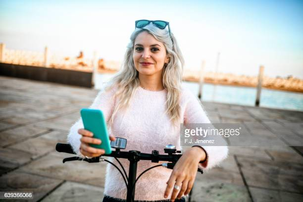 Woman with a bicycle and mobile phone