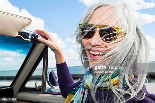 Woman with a big smile in a convertibel car.