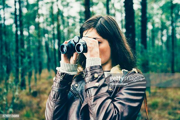Woman with a binocular is watching somebody or something