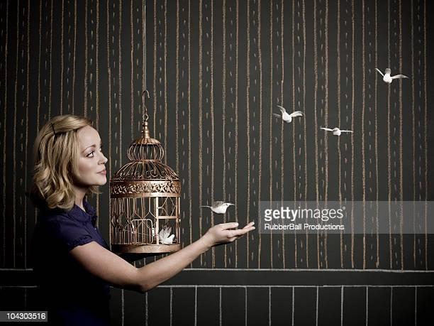 Femme avec une cage à oiseaux
