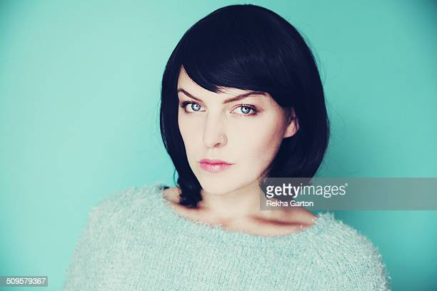 woman with a black bob on a light blue background - rekha garton stock pictures, royalty-free photos & images