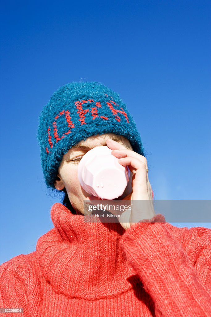 A woman with a blue hat drinking from a cup Sweden. : Stock Photo
