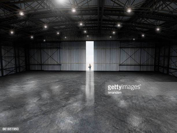 Woman with a blueprint in an empty warehouse by day