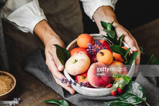 新鮮な果物のボウルを持つ女性 - 果物の盛り合わせ ストックフォトと画像