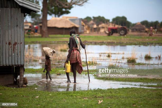 TOPSHOT A woman with a boy walk in a flooded area on May 31 in Panthau Northern Bahr al Ghazal South Sudan The rain is a threat for many farmers in...