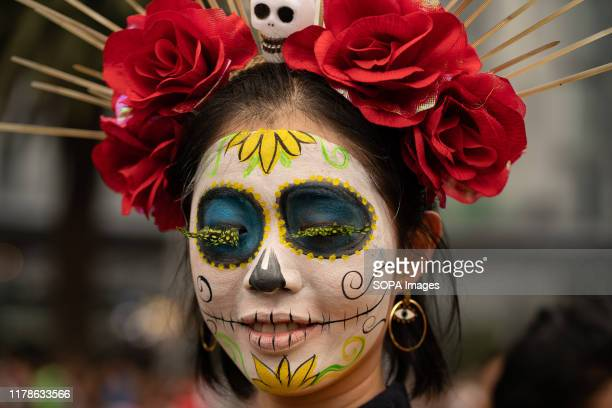 A woman with a brightly colored Catrina face paint poses for the camera during the Catrina Festival Thousands of people took to the streets of Mexico...