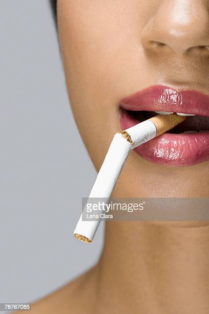 A woman with a broken cigarette in her mouth