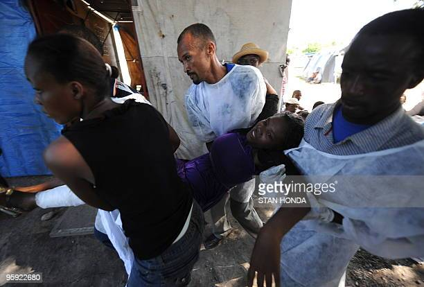 A woman with a broken leg is brought to a makeshift clinic in Leogane run by the 'cascos blancos' or white helmets an Argentinian medical group on...