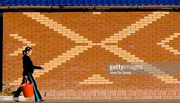 CONTENT] A woman with a bucket walks along the patterns of an orange brick wall in Kazakhstan