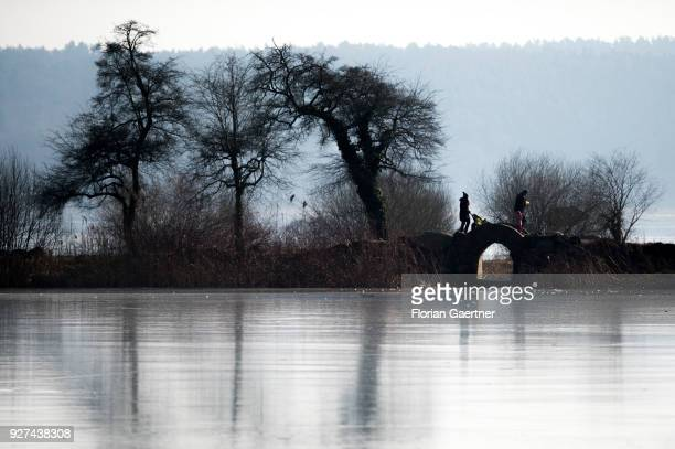 A woman with a buggy and a man with a child walk over a little bridge at a frozen lake near the lake Schwielowsee on March 03 2018 in Petzow Germany