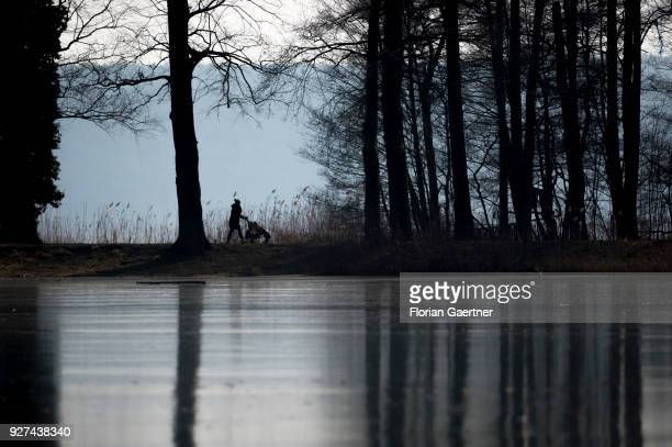 A woman with a buggy walks near the lake Schwielowsee on March 03 2018 in Petzow Germany
