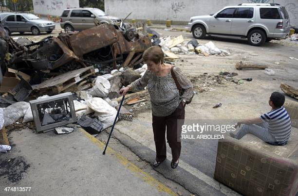 A woman with a cain walks next to a barricade during protests against the government of Venezuelan President Nicolas Maduro in Caracas on February 25...