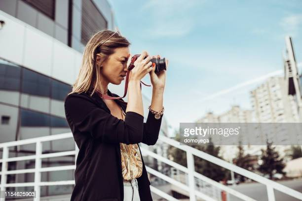 woman with a camera photographing in the city street - digital camera stock pictures, royalty-free photos & images