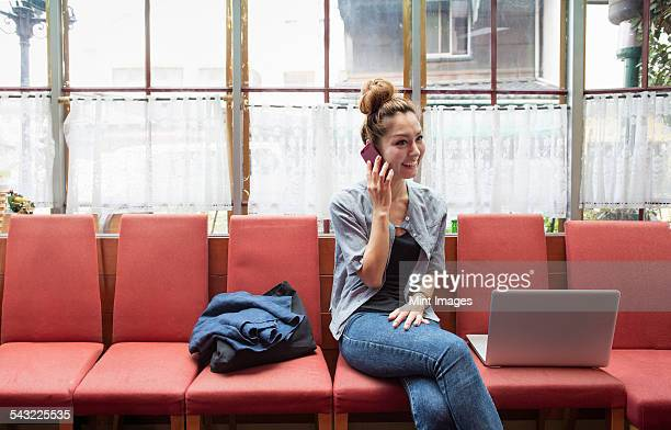 A woman with a cell phone and laptop, sitting indoors.
