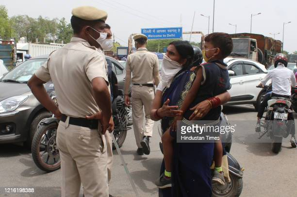 Woman with a child pleads her case with Haryana police personnel screening commuters at the Dundahera-Kapashera border, on May 29, 2020 in Gurugram,...