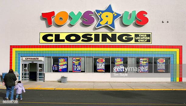 A woman with a child walks toward an entrance to a Toys R Us store January 10 2006 in Arlington Heights Illinois It was announced on Monday January 9...