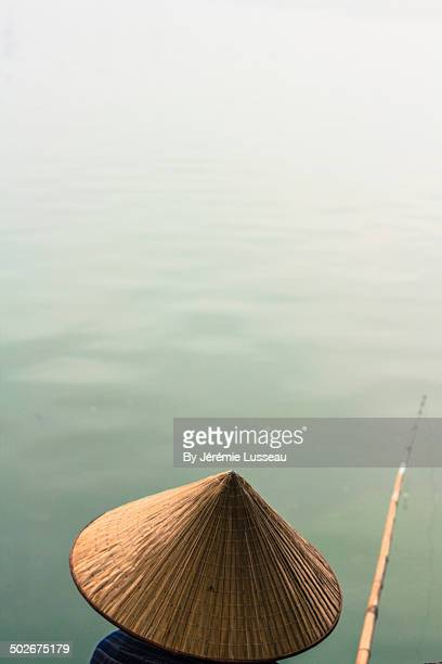 A woman with a chinese hat and a fishing pole