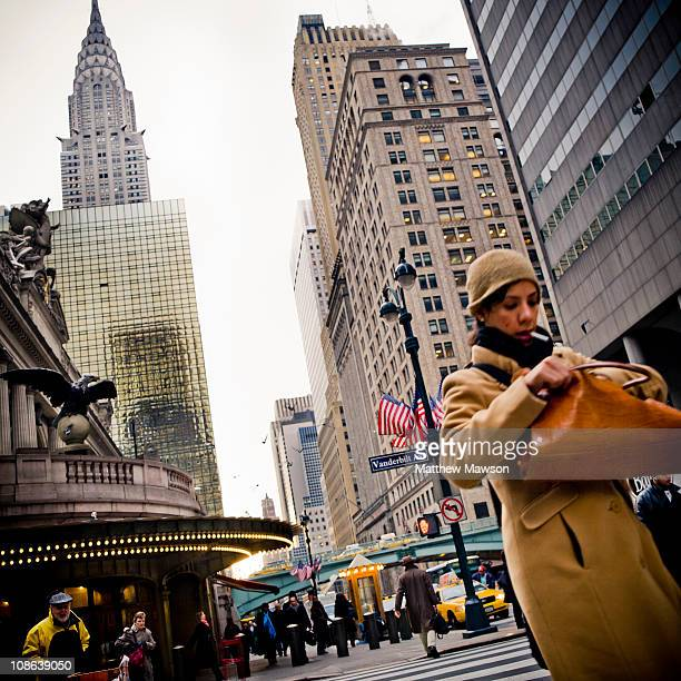 Woman with a cigarette in her mouth looking in her bag walks up E 42nd Street passing Grand Central Station and Vanderbilt Avenue. The Chrysler...