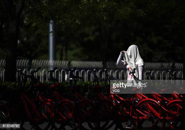 A woman with a clothes on head walks past the sharing bikes on July 12 2017 in Beijing China The dog days of summer start from July 12 in China