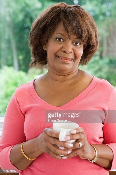 woman with a coffee cup - alleen één oudere vrouw stockfoto's en -beelden
