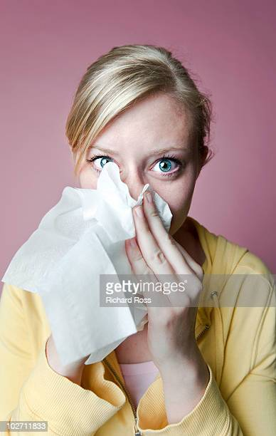 woman with a cold / allergies blowing her nose - handkerchief stock pictures, royalty-free photos & images