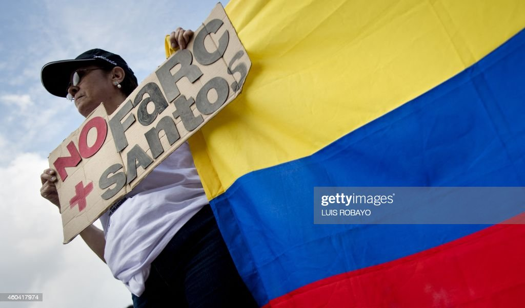 A woman with a Colombian national flag takes part in a march against the current peace talks with FARC rebels in Cali, Department of Valle del Cauca, Colombia, on December 13, 2014. Hundreds of people marched Saturday in several cities in Colombia to question the peace negotiations between the government of President Juan Manuel Santos and the FARC guerrillas.