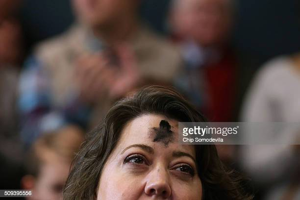 A woman with a cross on his forehead for Ash Wednesday listens to Republican presidential candidate Sen Marco Rubio during a campaign rally at the...