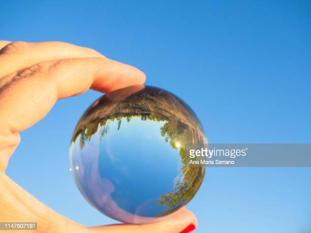 a woman with a crystal ball in her hand with a reflection of a rural landscape. ecology concept - virada ao contrário - fotografias e filmes do acervo
