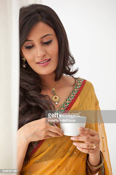 Woman with a cup of coffee looking out a window