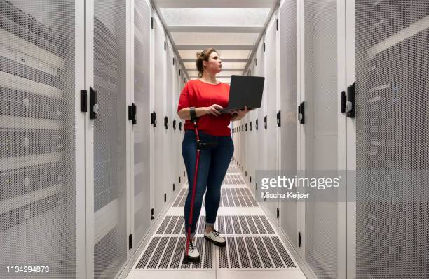 woman with a damaged hip joint working in data centre - differing abilities female business stock pictures, royalty-free photos & images