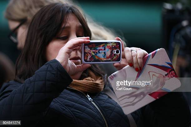 A woman with a David Bowie iPad and iPhone case photographs a mural of David Bowie in Brixton on January 11 2016 in London England British music and...