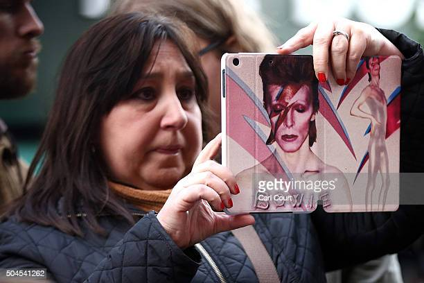A woman with a David Bowie iPad case photographs a mural of David Bowie in Brixton on January 11 2016 in London England British music and fashion...